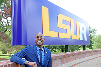 Stephan Moore by LSUA sign